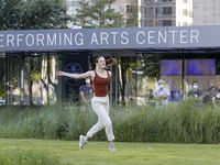"""Dancer Taylor Kinsey moves along the grass during a performance of """"The Great 30"""" outside the AT&T Performing Arts Center in downtown Dallas on Thursday, Aug. 12, 2021."""