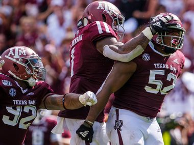 Texas A&M defensive lineman Justin Madubuike (52) celebrates with linebacker Buddy Johnson (1) and defensive lineman Jayden Peevy (92) after a defensive stop during the second quarter of an NCAA football game against Auburn at Kyle Field on Saturday, Sept. 21, 2019, in College Station, Texas. (Smiley N. Pool/The Dallas Morning News)