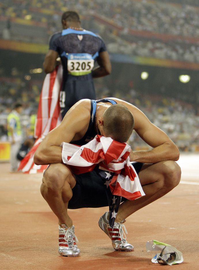 2008 Beijing Olympics: Jeremy Wariner puts his head in a U. S. flag given to him by LaShawn Merritt (background) after coming in second to Merritt in the Men's 400 meter final at the National Stadium  in Beijing, China Thursday August 21, 2008.