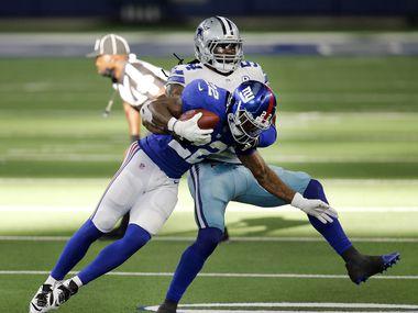 Dallas Cowboys middle linebacker Jaylon Smith (54) takes down New York Giants running back Wayne Gallman (22) during the third quarter at AT&T Stadium Stadium in Arlington, Texas, Sunday, October 11, 2020.