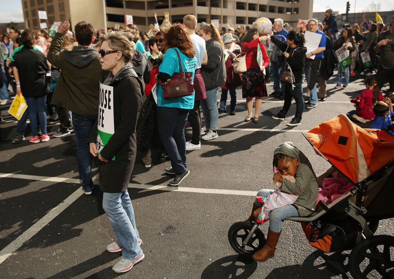 Abigail Burke, 3, of Arlington, Texas, sits in a stroller as anti-abortion activists speak in a parking lot adjacent to the Earle Cabell Federal Building at the rally portion of the North Texas March for Life in Dallas Saturday.