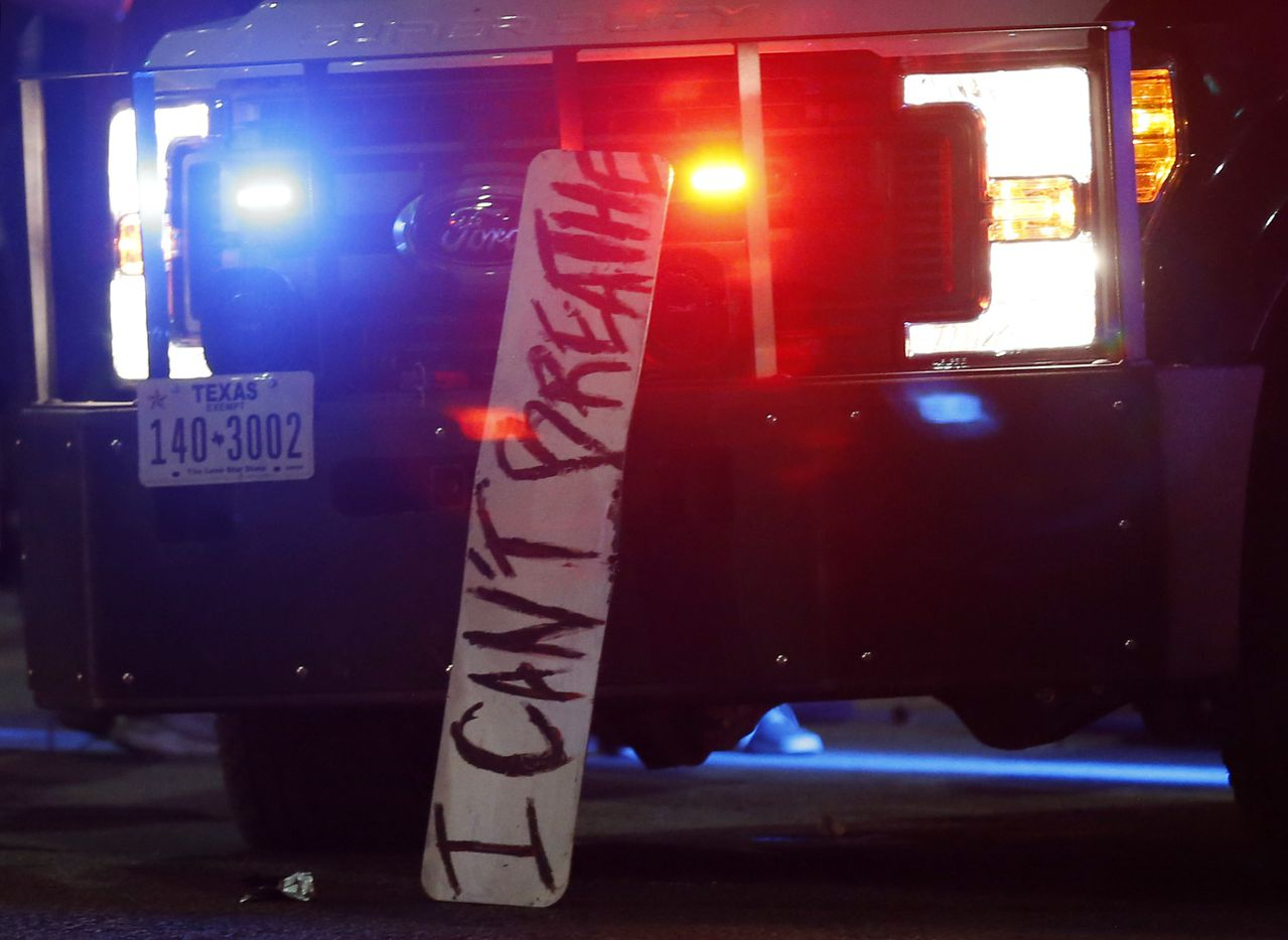 """A sign stating """"I Can't Breathe,"""" rests on the front of a Dallas police vehicle as protesters march during a demonstration against police brutality in downtown Dallas, on Friday, May 29, 2020. George Floyd died in police custody in Minneapolis on May 25."""