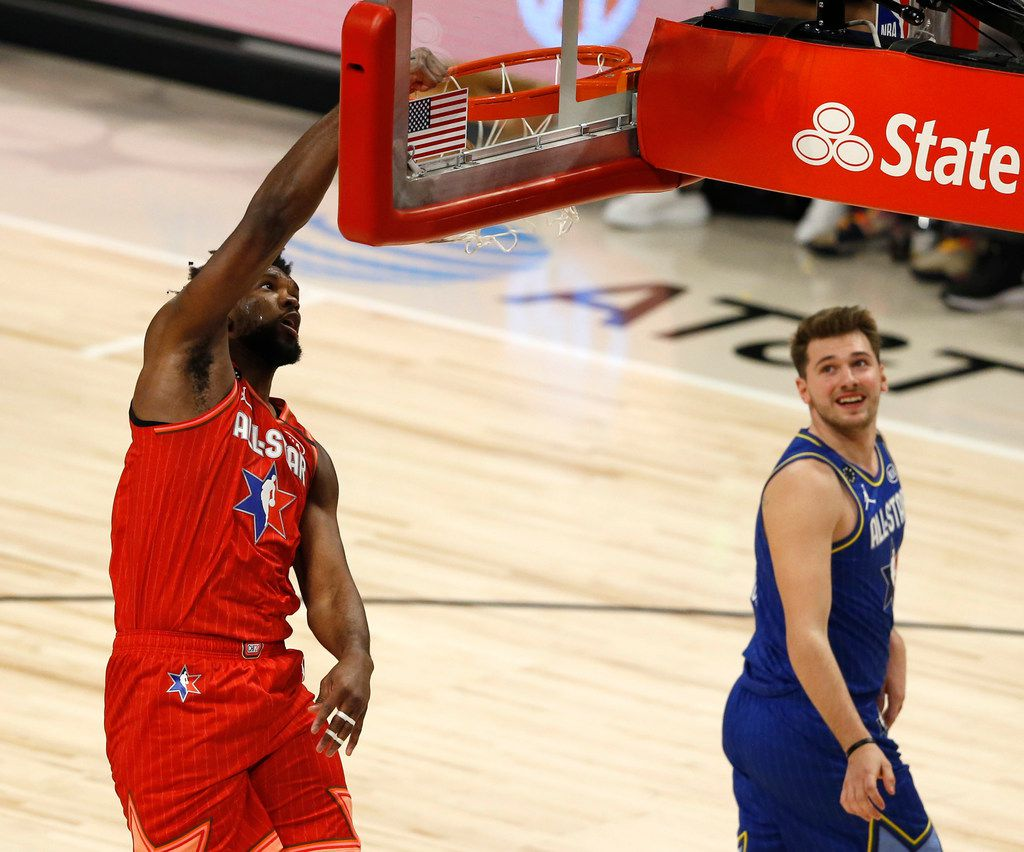 Team Giannis' Joel Embiid (24) dunks as Team LeBron's Luka Doncic (2) watches during the second half of play in the NBA All-Star 2020 game at United Center in Chicago on Sunday, February 16, 2020. Team LeBron defeated Team Giannis 157-155. (Vernon Bryant/The Dallas Morning News)