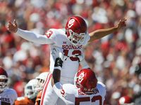 Oklahoma offensive lineman Tyrese Robinson (52) lifts Oklahoma quarterback Caleb Williams (13) into the air in celebration of Williams' touchdown during the first half of an NCAA college football game against Texas at the Cotton Bowl in Fair Park, Saturday, October 9, 2021.