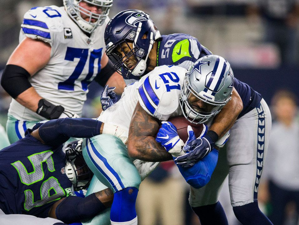FILE - Cowboys running back Ezekiel Elliott (21) is tackled by Seahawks linebackers Jake Martin (59) and K.J. Wright (50) during the fourth quarter of an NFC wild-card playoff game on Saturday, Jan. 5, 2019, at AT&T Stadium in Arlington.