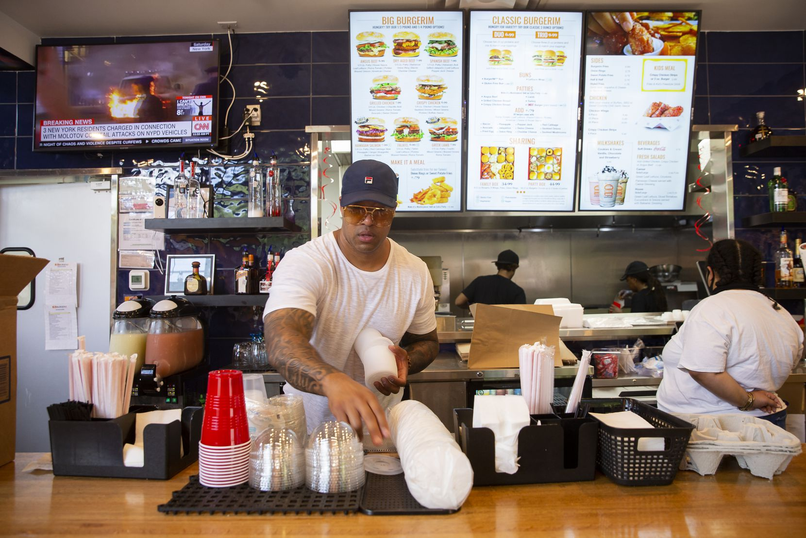 Owner Wes Williams restocks lids at BurgerIM on Sunday, May 31, 2020 in Dallas. Many in the community have shown up to support the West End restaurant after it was damaged by protesters Friday night. (Juan Figueroa/ The Dallas Morning News)