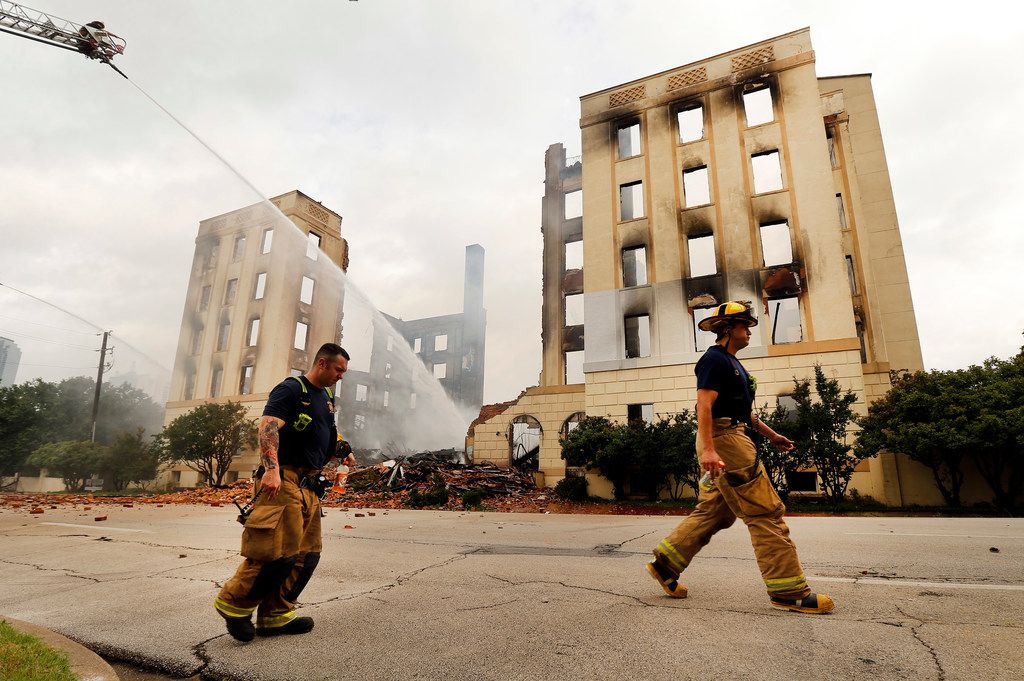 Dallas firefighters walk past the destroyed historic Ambassador Hotel just south of downtown Dallas.