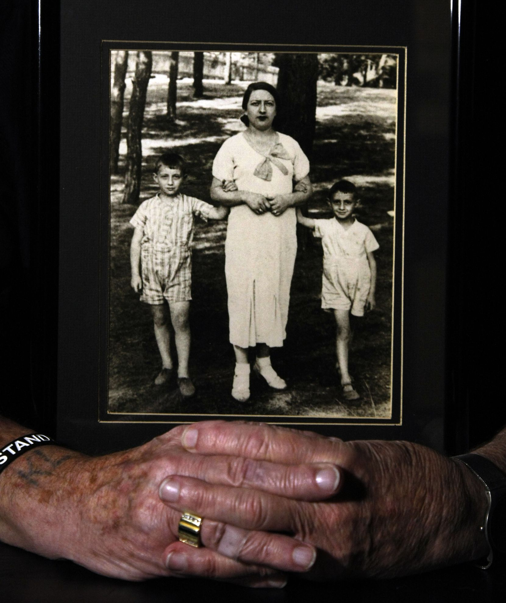 Max Glauben, a longtime Dallas resident who is a Holocaust survivor, wears his Upstander wristband next to his KL tattoo, which stands for Concentration Camp, in German. He holds a photo of himself (left) when he was 10, with his younger brother, Heniek, 8, (right) and their mother, mother, Faiga (which is Yiddish, or Fela, in Polish), that was taken in Poland in 1936. Photographed on July 29, 2011.  (Staff photo)