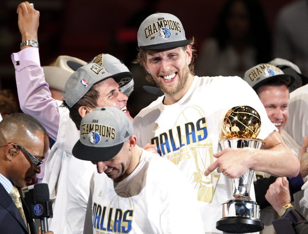 Dallas Mavericks' Dirk Nowitzki (41) holds the Bill Russell NBA Finals MVP trophy as he, Mavs owner Mark Cuban, Mavs point guard Jason Kidd (2) (front left) and others celebrate after the Mavs won the NBA Championship at the American Airlines Arena in Miami, Florida, June 12, 2011.