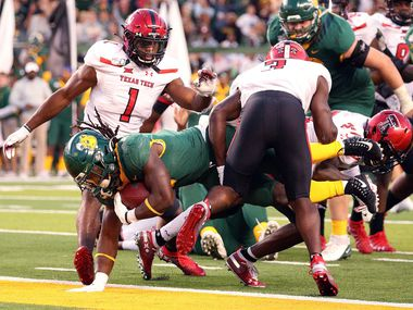 WACO, TEXAS - OCTOBER 12: JaMycal Hasty #6 of the Baylor Bears dives into the end zone past Douglas Coleman III #3 of the Texas Tech Red Raiders to score the game-winning touchdown in overtime on October 12, 2019 in Waco, Texas.