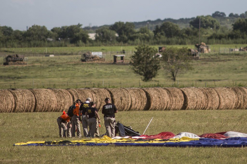 Investigators at the site where a hot air balloon crashed, killing 16 people, west of Lockhart, Texas, July 30, 2016. Officials said the craft caught fire in midair and plummeted to the ground in what appeared to be the worst balloon accident in U.S. history. (Tamir Kalifa/The New York Times)