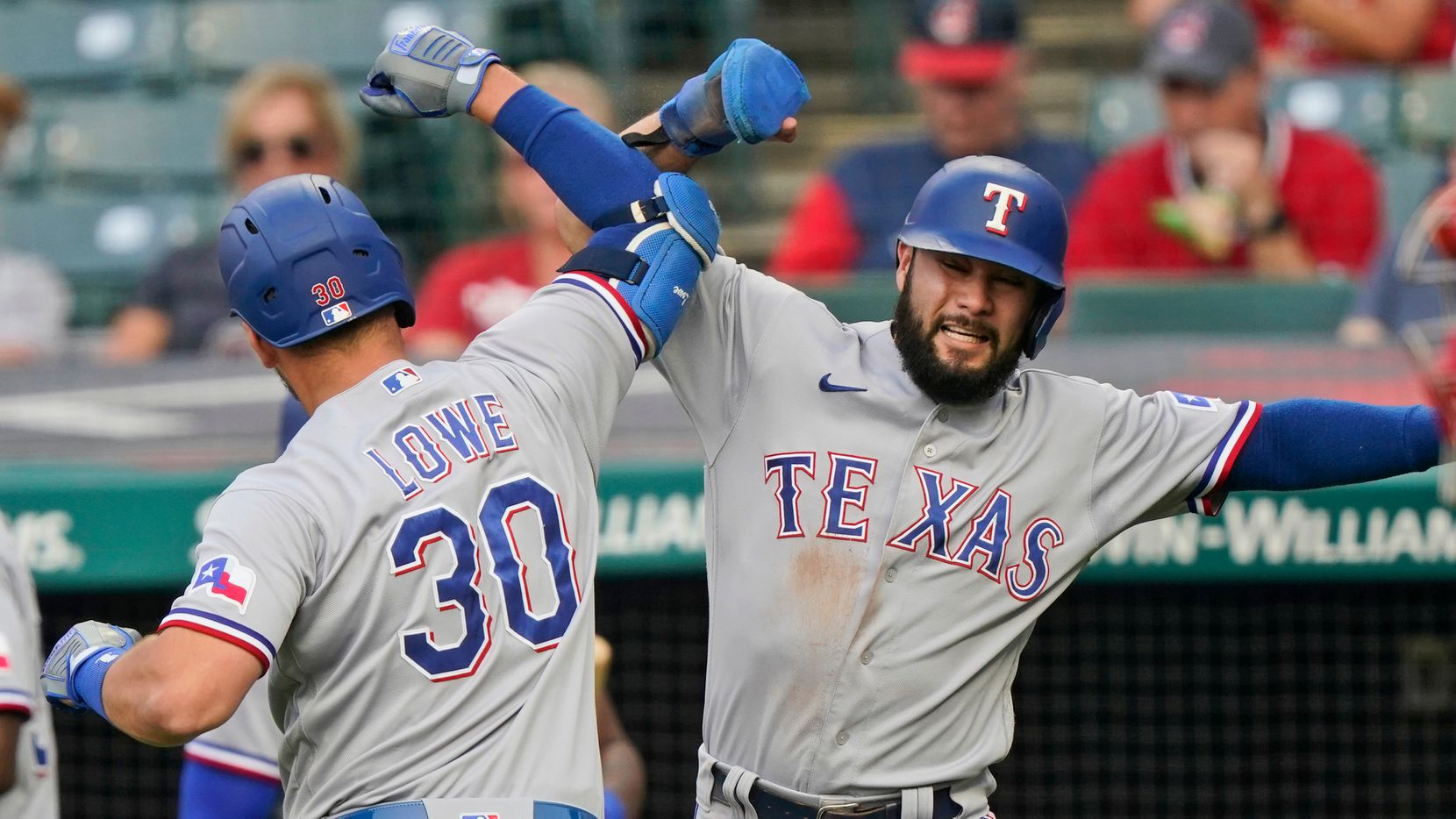 Texas Rangers' Isiah Kiner-Falefa, right, congratulates Nathaniel Lowe after Lowe hit a three-run home run in the first inning of a baseball game against the Cleveland Indians, Tuesday, Aug. 24, 2021, in Cleveland. (AP Photo/Tony Dejak)
