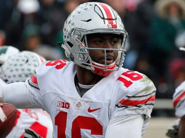 FILE - In this Saturday, Nov. 19, 2016, file photo, Ohio State quarterback J.T. Barrett looks to throw against Michigan State during the fourth quarter half of an NCAA college football game in East Lansing, Mich.