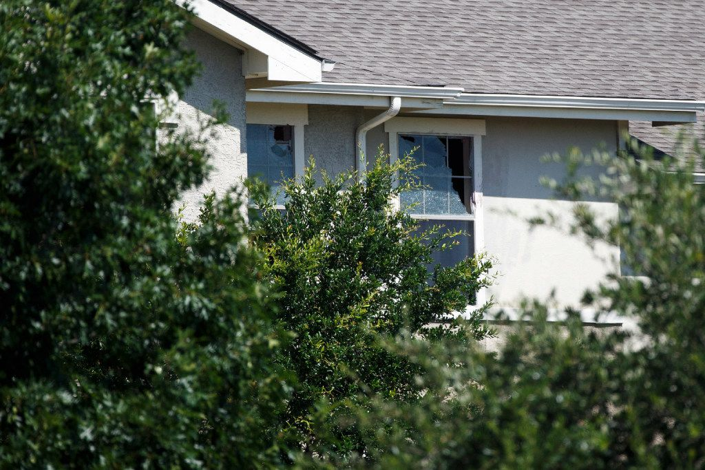Broken apartment windows are seen near where Dallas Police Department SWAT work the scene where someone shot at officers attempting to make an arrest at an east Oak Cliff apartment complex, police said, on Thursday, July 13, 2017, in Dallas.