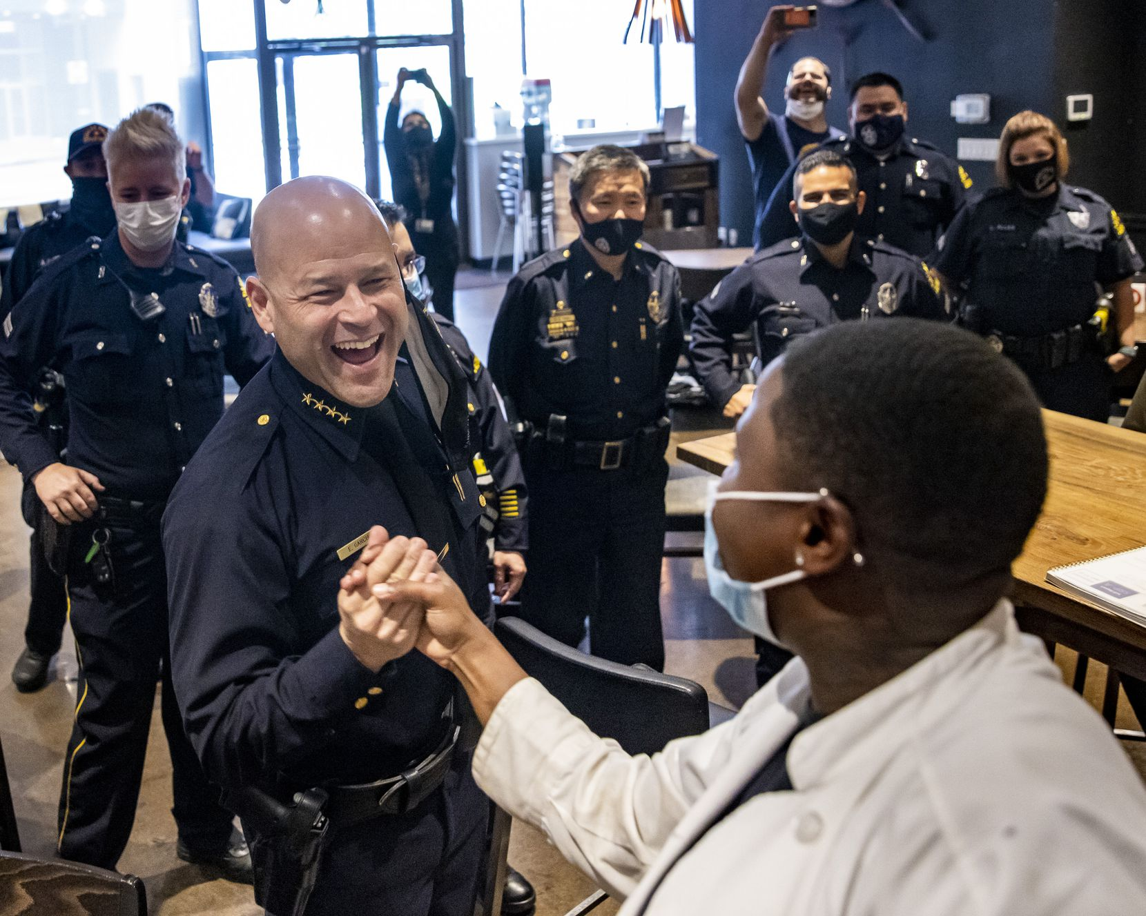 """Dallas Police Chief Eddie García — aka """"the dish-washing guy"""" — surprises intern Keanna Adams at Cafe Momentum in downtown Dallas on May 18. Dallas police officers revealed themselves after they spent a shift incognito as volunteers working with the restaurant's interns. (Lynda M. González/The Dallas Morning News)"""