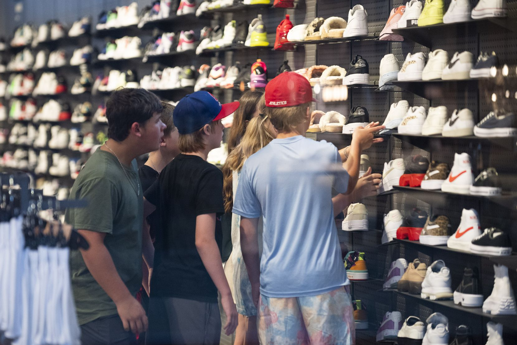 A group of teens browses the shoes inside Finish Line at NorthPark Center in Dallas.