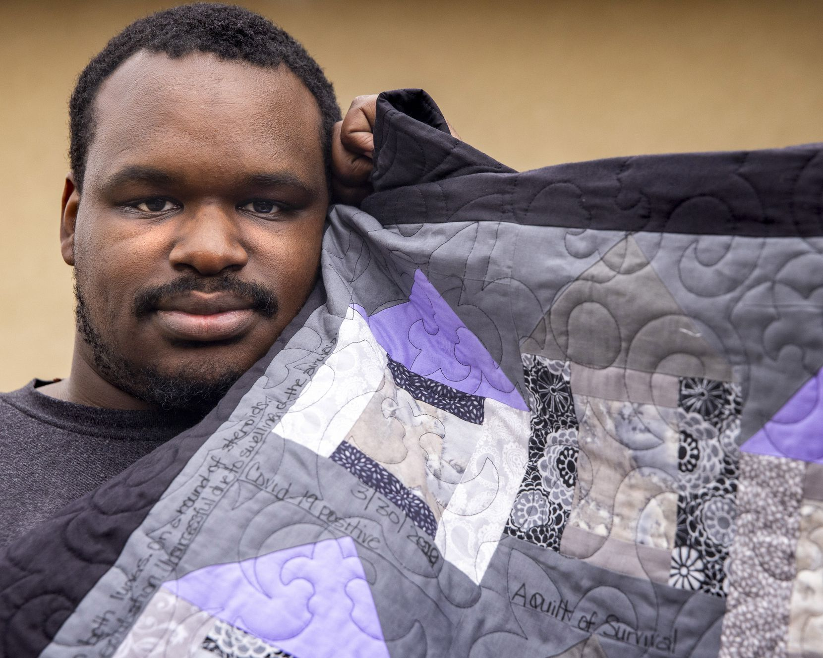 Kerry Parks poses with the survivor's quilt that his mother-in-law, Marva Stephens, began sewing for him shortly after he was released from Parkland.