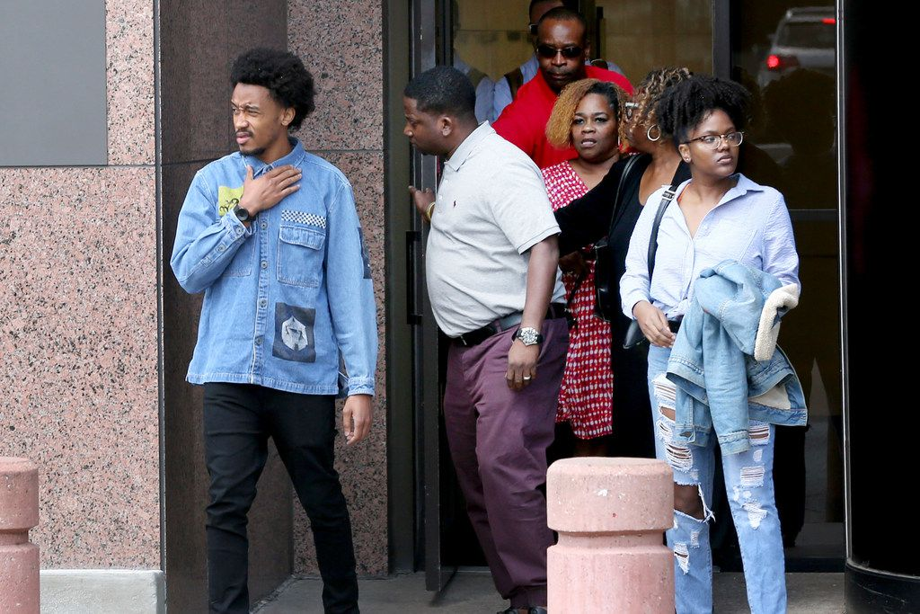 Sandra Harper (center) and her son Tony Harper (holding door) emerged from the federal courthouse in downtown Dallas with other family members on Wednesday. Harper sued the city of Dallas and a former police officer for fatally shooting her son in July 2012.