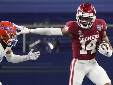 Oklahoma wide receiver Charleston Rambo (14) pushes past Florida defensive back Donovan Stiner (13) during the first half of the Cotton Bowl Classic at AT&T Stadium on Wednesday, Dec. 30, 2020, in Arlington.