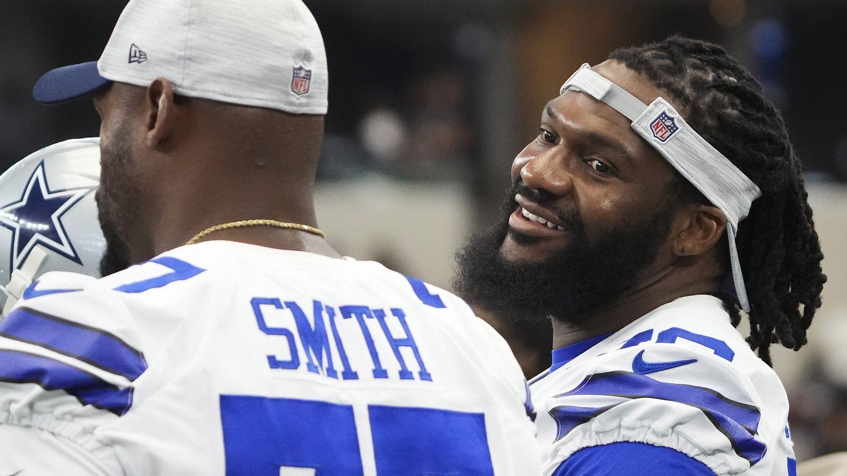 El tackle ofensivo de los Cowboys de Dallas, Ty Nsekhe (der), habla con el tackle ofensivo Tyron Smith (77)  durante el partido de pretemporada  contra los Jaguars de Jacksonville en el AT&T Stadium, el domingo 29 de agosto de 2021 en Arlington.
