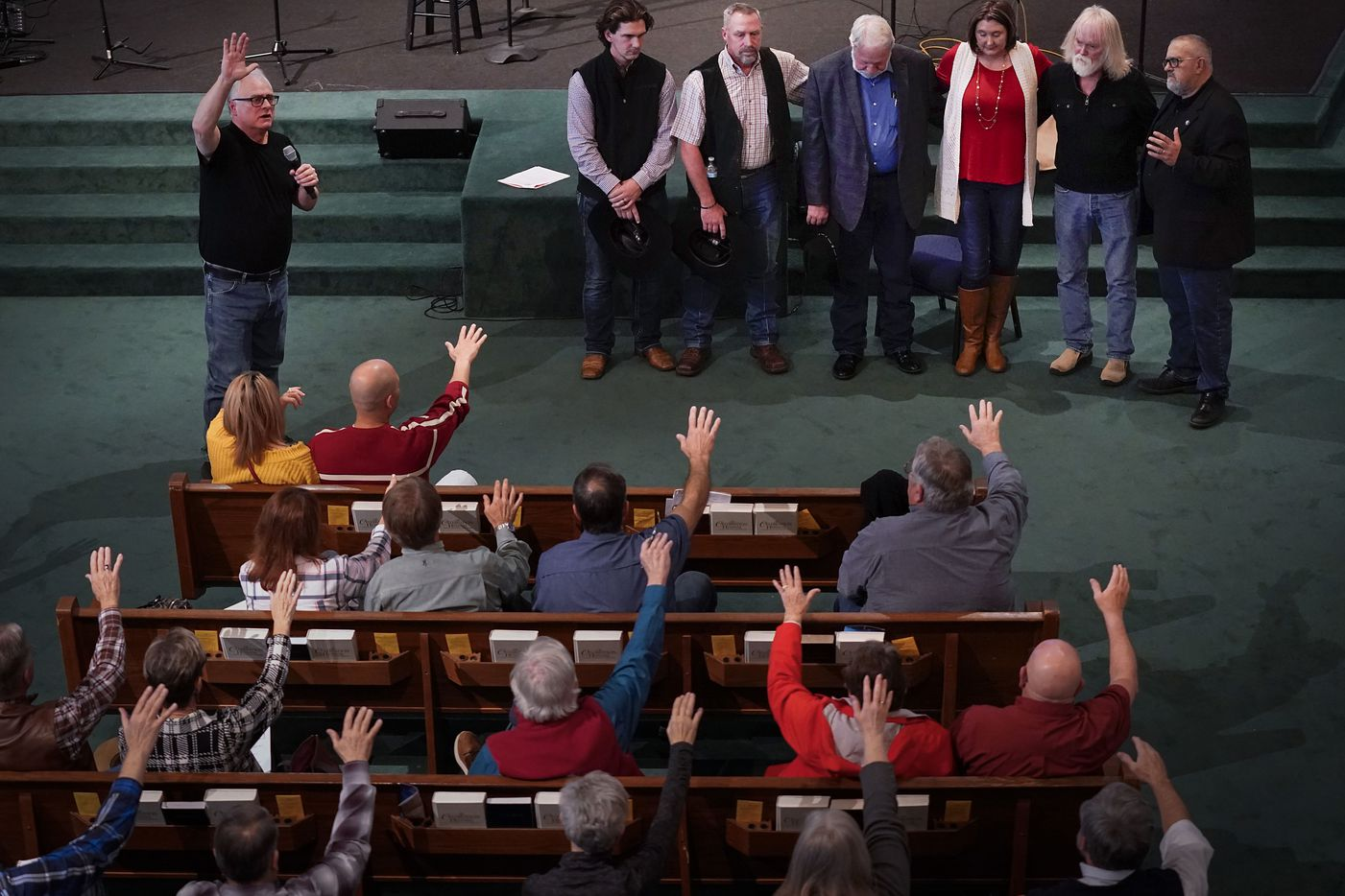 Jimmy Meeks (top left) leads a prayer for members of the West Freeway Church of Christ volunteer security team, including Jack Wilson (at center of group wearing jacket) who stopped a gunman at the church in White Settlement, during a church safety seminar at North Pointe Baptist Church on Sunday, Jan. 26, 2020, in Hurst, Texas.