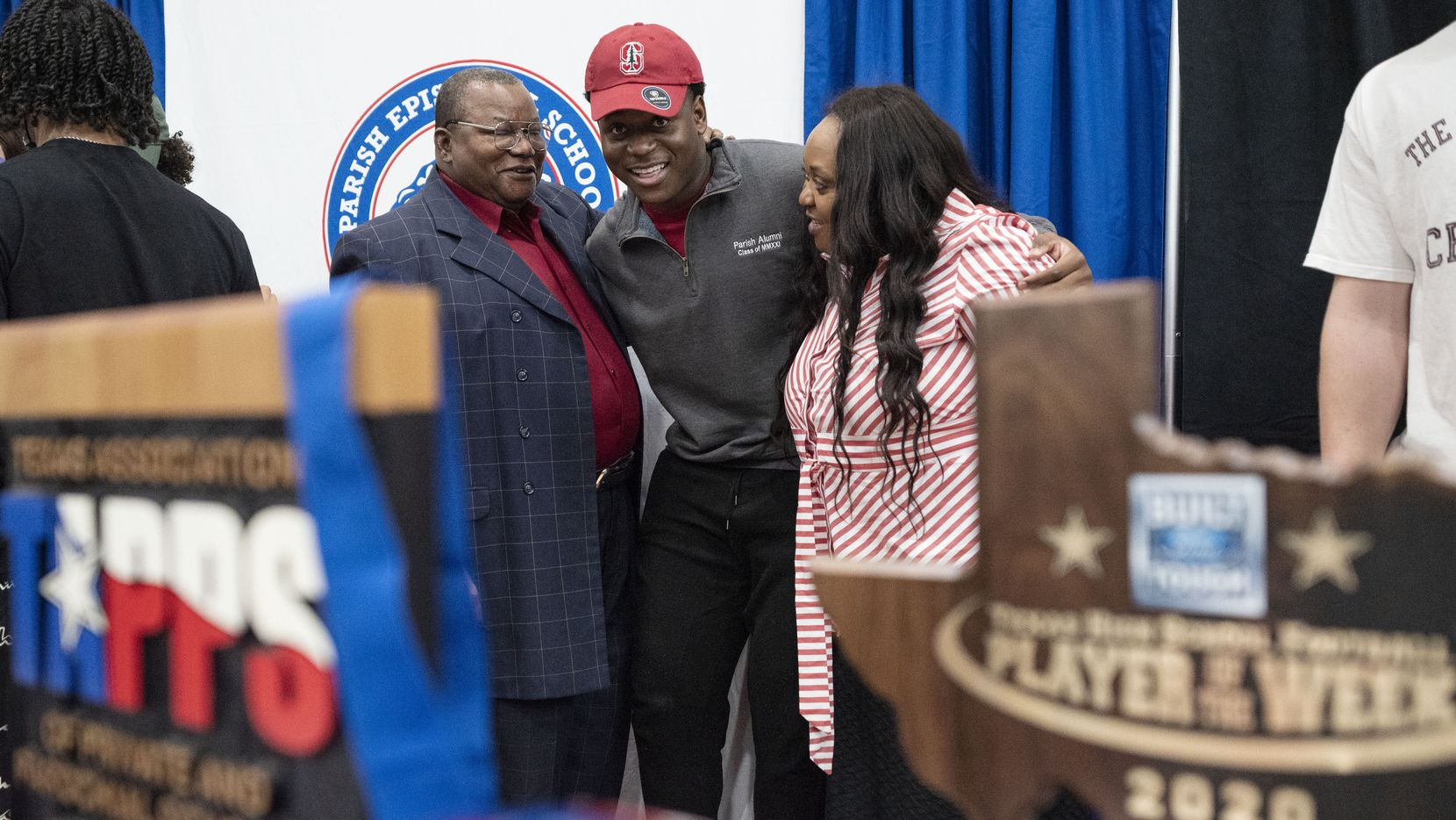 Senior Austin Uke is hugged by his parents Augustine Uke, left, and his mother Irene Uke, as the senior signed his letter of intent to play football for Stanford University during National Signing Day, on Wednesday, Feb. 02, 2021 at Parish Episcopal School in Dallas.