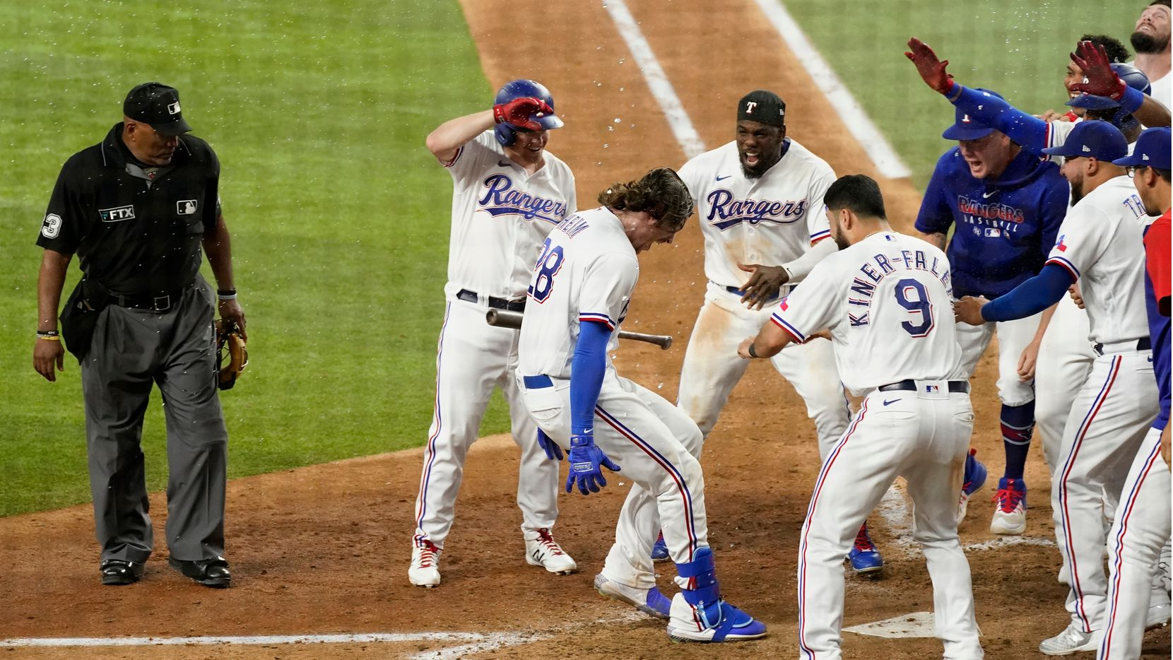 Umpire Laz Diaz, left, watches as Texas Rangers' Jonah Heim (28) approaches the plate after hitting a two-run home run in the 10th inning of the team's baseball game against the Seattle Mariners in Arlington, Texas, Saturday, July 31, 2021. (AP Photo/Tony Gutierrez)