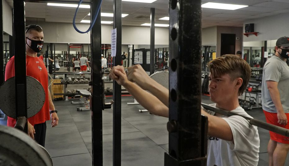 Coach Jared Hudgins (left) looks on as Brycen Alexander does a squat routine during the day of workouts at Fort Worth Christian School in North Richland Hills, Texas on Thursday, June 4, 2020. The athletes participated in several drills on field as well as weight training.