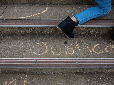 """Demonstrators write with chalk on the stairs leading up to the Collin County Courthouse following a press conference on April 28, 2021 including updates on Marvin Scott III's death. Collin County NAACP president June Jenkins said the incident contributed to one of the """"most unfortunate"""" years the branch has experienced so far."""