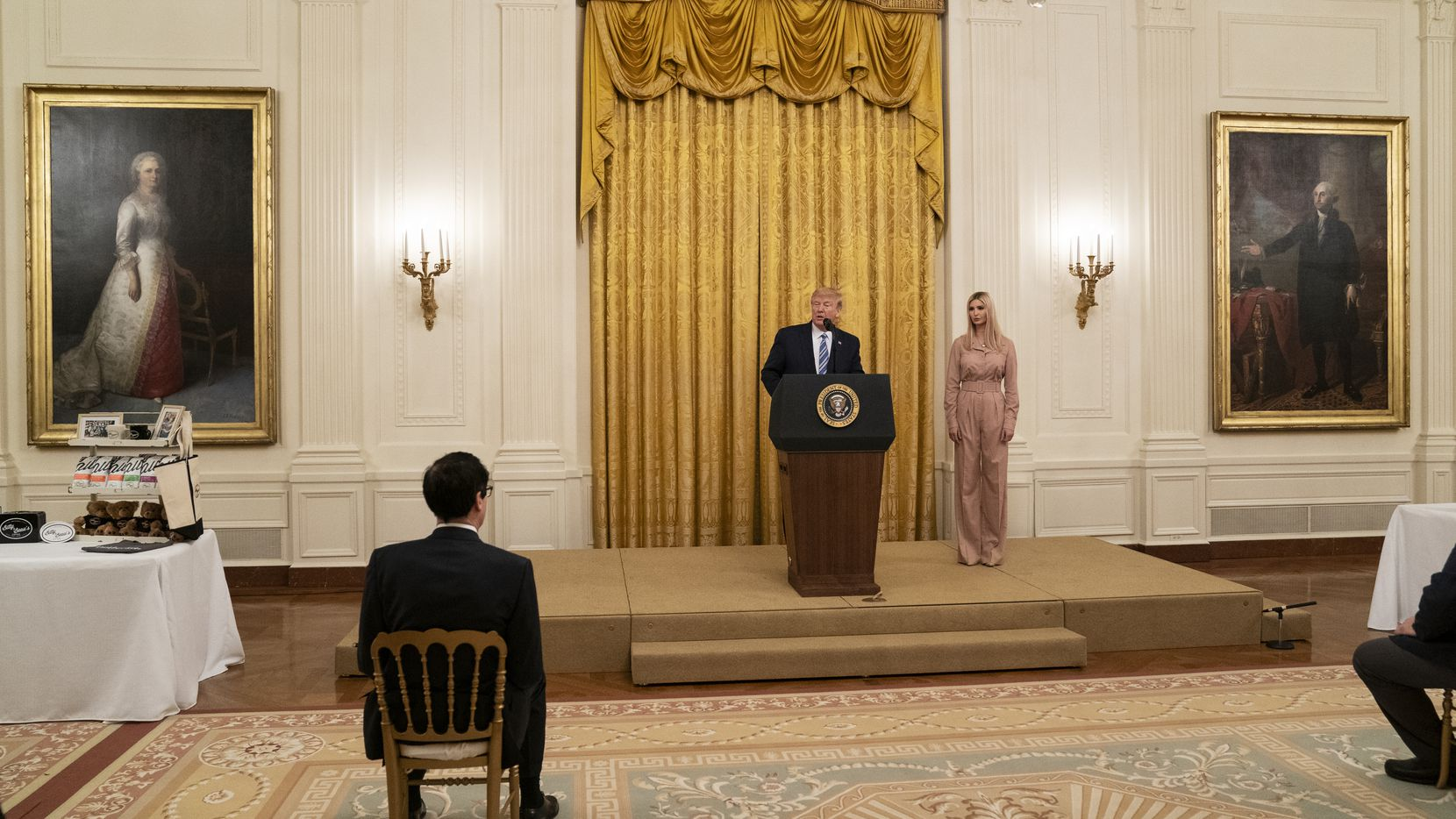 Treasury Secretary Steven Mnuchin, left, and Ivanka Trump listen as President Donald Trump speaks during an event about the Paycheck Protection Program used to support small businesses during the coronavirus outbreak, in the East Room of the White House, Tuesday, April 28, 2020, in Washington. (AP Photo/Evan Vucci)