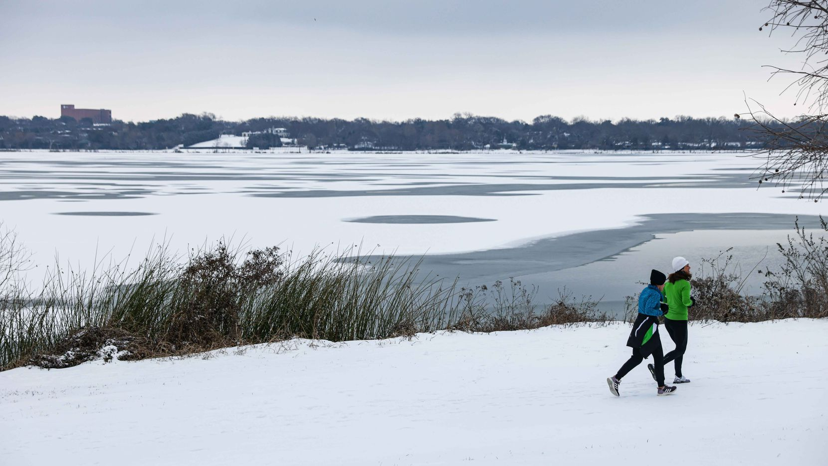 A couple of women jogged Feb. 17 on the snow that fell during an overnight storm at White Rock Lake in Dallas.