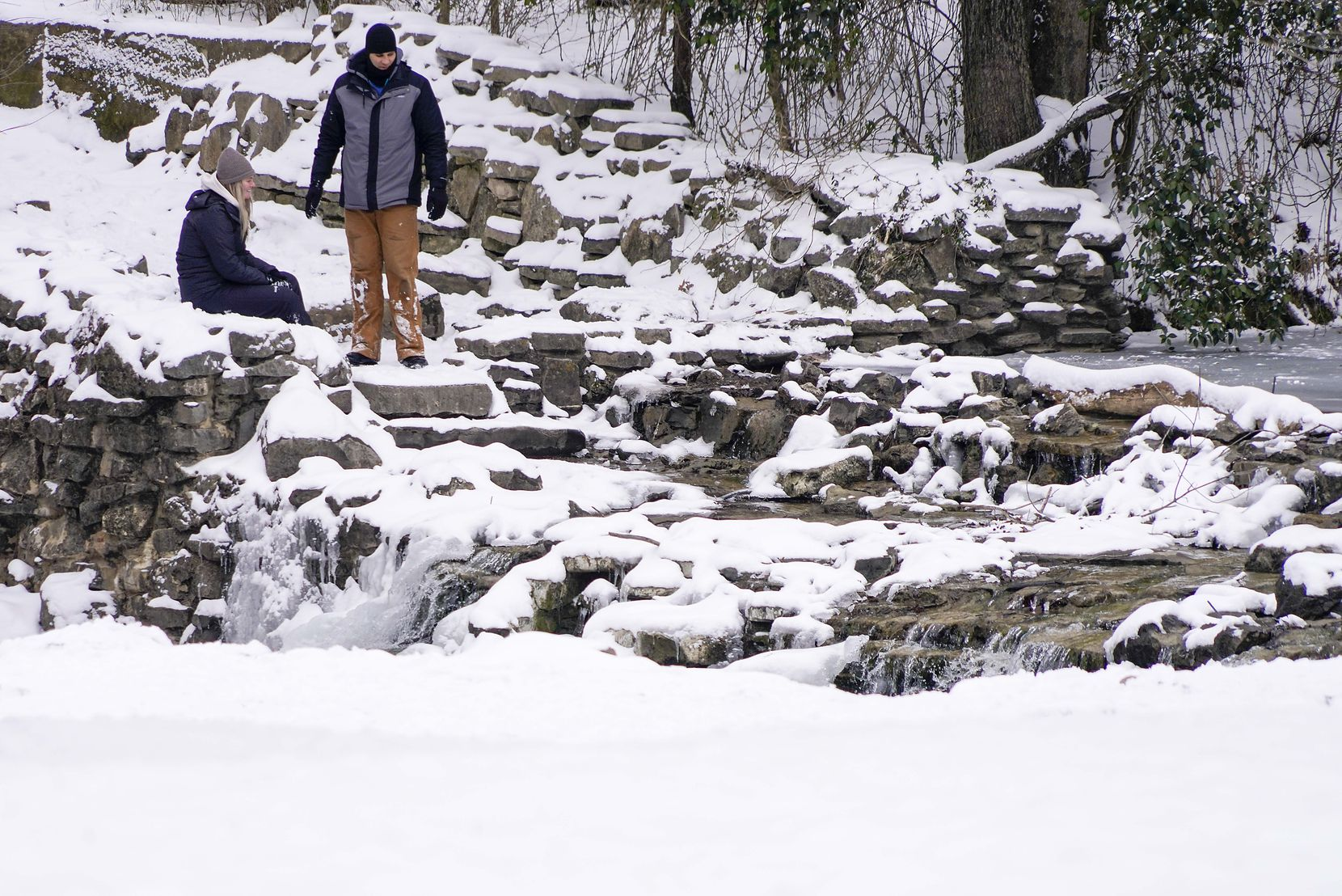 People check out the partially frozen waterfall in Prairie Creek Park after a second winter storm brought more snow and continued freezing temperatures to North Texas on Wednesday, Feb. 17, 2021, in Richardson.
