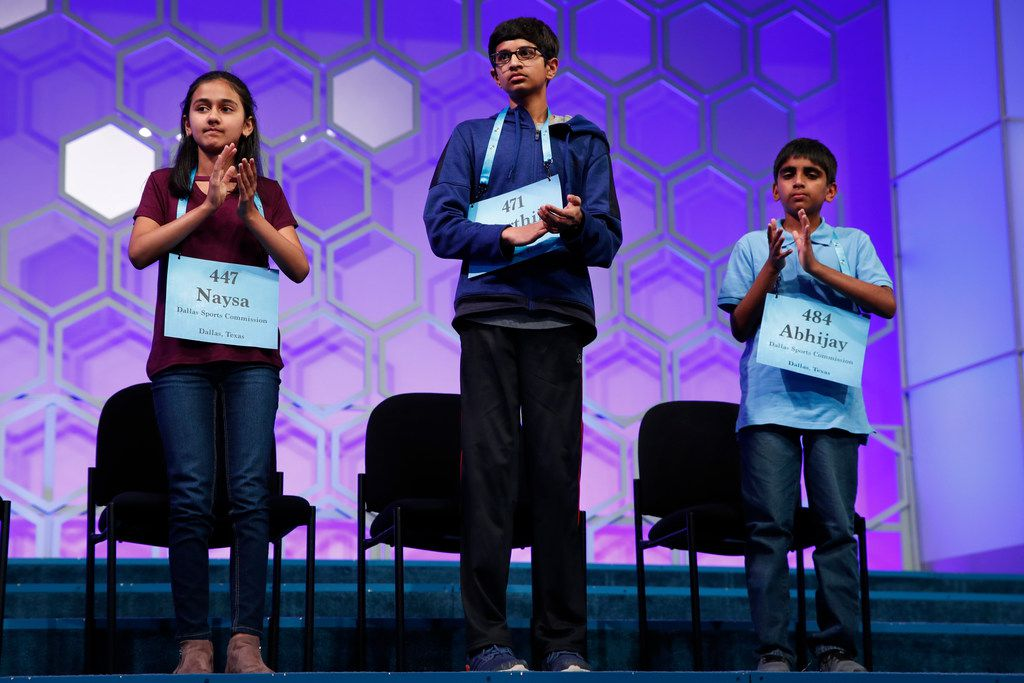The final three competitors in the Scripps National Spelling Bee, from left, Naysa Modi, 12, from Frisco, Texas, Karthik Nemmani, 14, from McKinney, Texas, and Abhijay Kodali, 11, from Flower Mound, Texas, applaud during the bee in Oxon Hill, Md., Thursday, May 31, 2018. They placed second, first, and third, respectively. (AP Photo/Jacquelyn Martin)