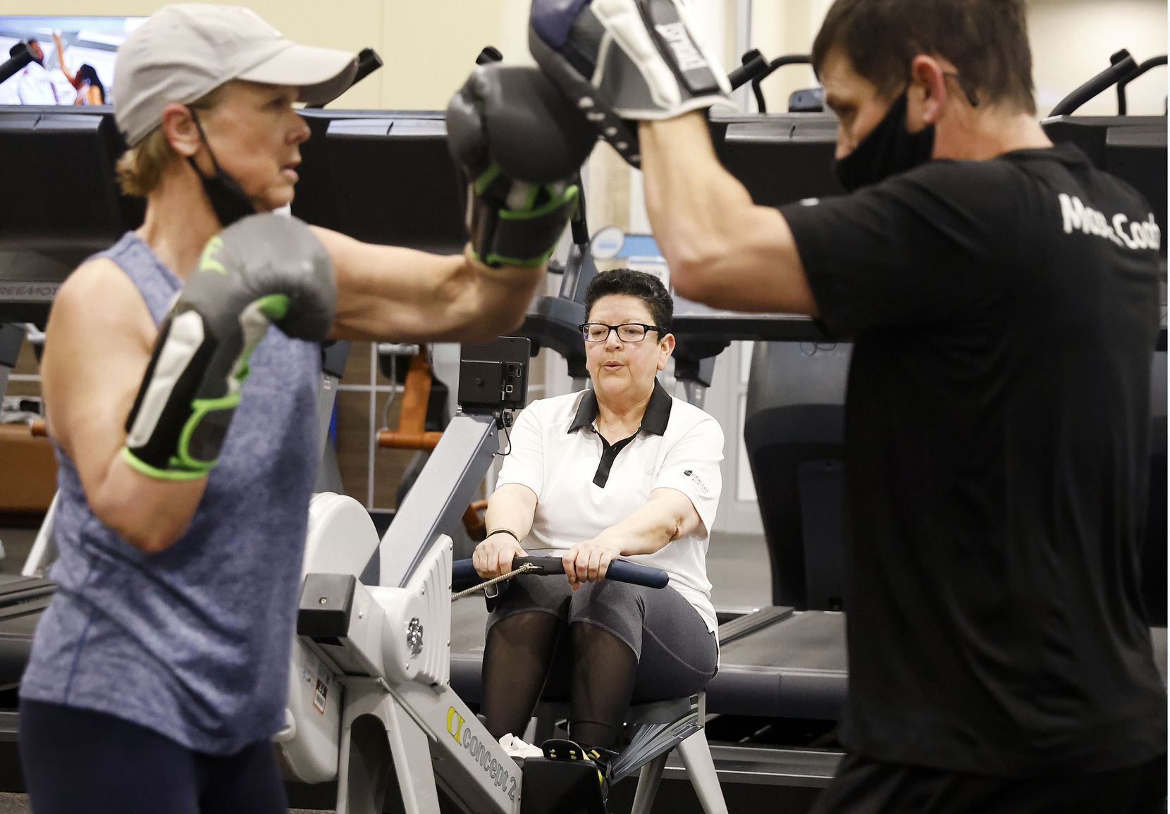 Gym member Melba Siebel of McKinney works out on a rowing machine while trainer Brent Wade and customer Kelli Kocher of Lewisville wear masks to work out at 24 Hour Fitness in McKinney.