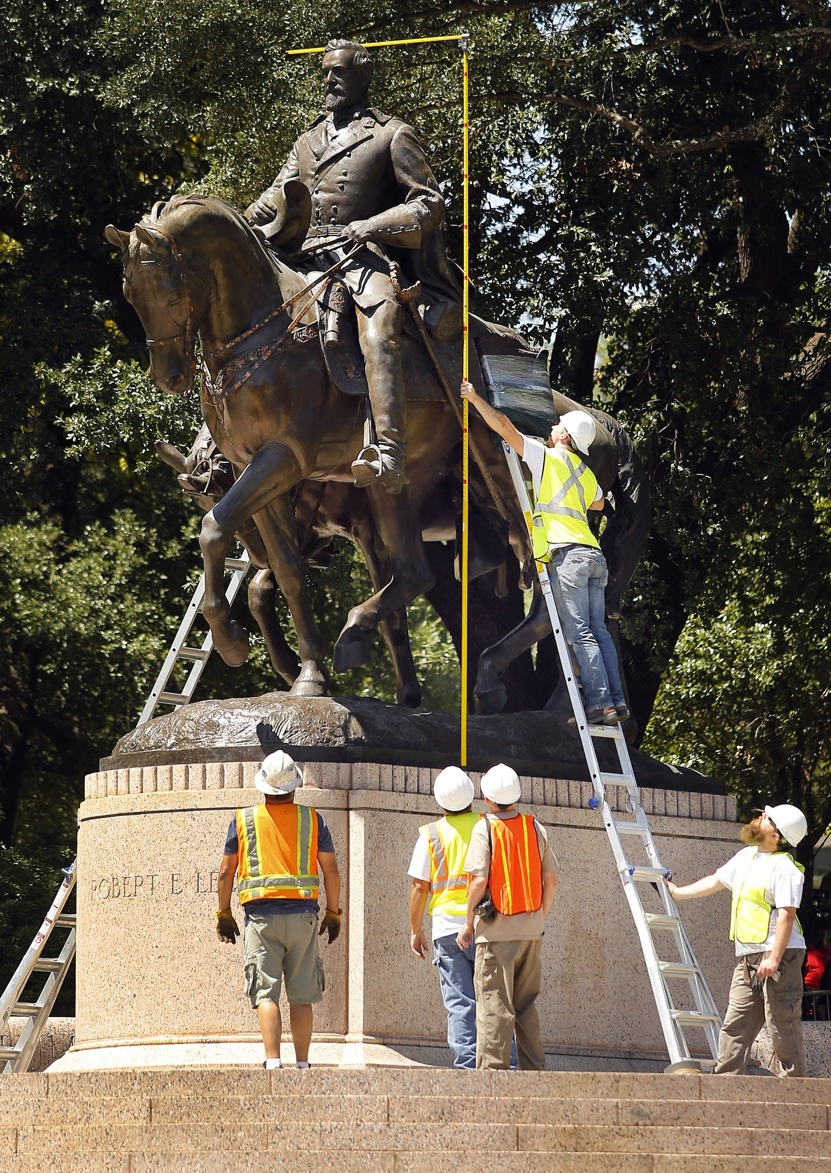 Crewmen from Howell Crane and Rigging Inc measure the height of the Robert E. Lee statue on Sept.  6, 2017.