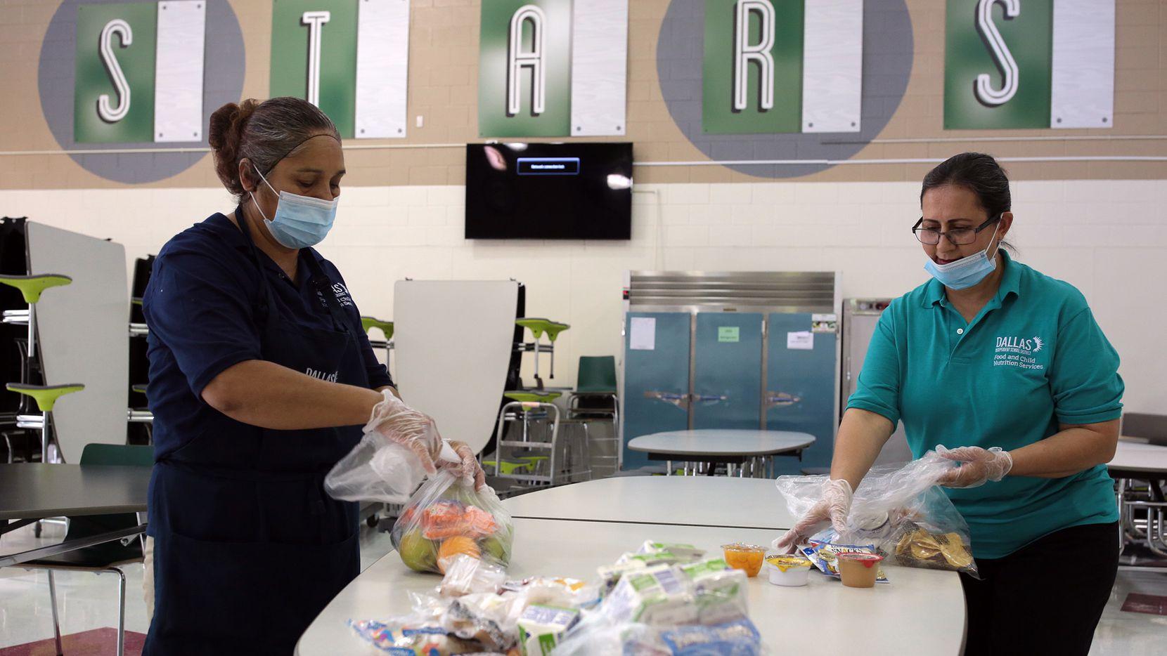 María Lorena Trejo (izq.), de la cafetería del DISD junto a su supervisora Adela Sánchez preparan las comidas del programa de alimentos de verano en la secundaria Raúl Quintanilla.