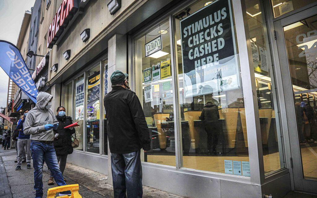 En imagen del 24 de abril de 2020, un grupo de personas mantiene el distanciamiento social y usa cubrebocas en medio de la propagación de covid-19, mientras esperan entrar a un centro de canje de cheques en Brooklyn, vecindario de la ciudad de Nueva York.