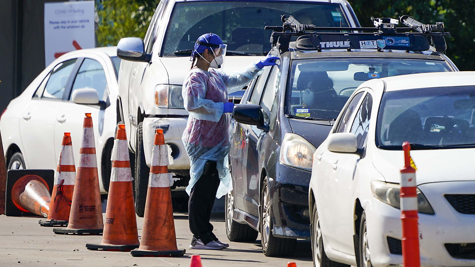 A health care worker interacts with motorists at a drive through COVID-19 testing facility at CitySquare on Wednesday, June 17, 2020, in Dallas. The COVID-19 testing center in South Dallas is a partnership between the City of Dallas, Dallas County, CitySquare and Kroger Health.