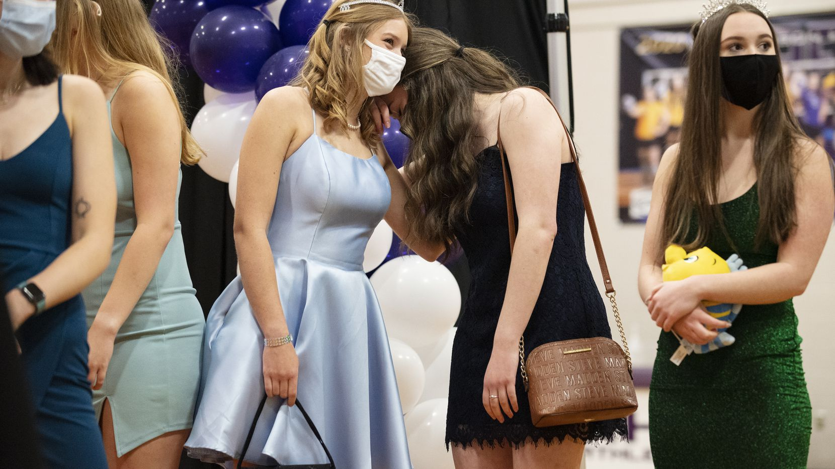 "Senior Gracie Oliver, center, reacts by hiding her head behind friend senior Caroline Patton while watching a slideshow with Hanna Ramsey, far-right, during an event titled ""Walk Down Memory Lane"" for Richardson High School graduates, on Saturday, April 24, 2021 at Richardson High School. The event showcased a slideshow of RHS senior, a red carpet experience, a live DJ and plenty of photo opportunities for seniors."