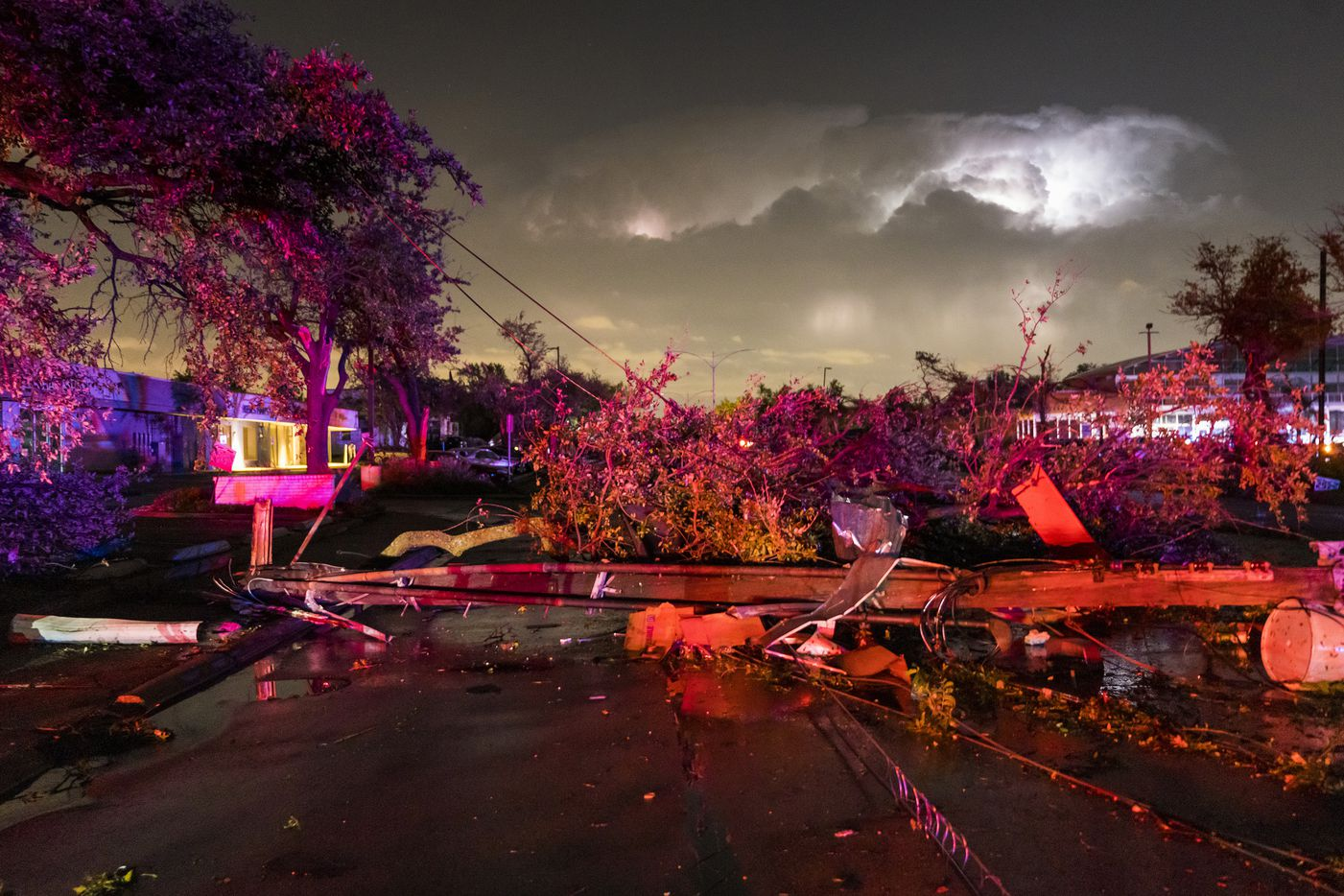 Downed power lines and trees block Royal near the intersection at Preston from tornado damage as lightening flashes to the east on Sunday, Oct. 20, 2019, in Dallas.