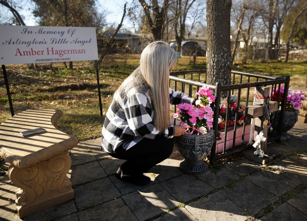 Amber Hagerman's mother Donna Williams places new flowers at a permanent memorial for her daughter at the abduction site in E. Arlington, Texas, Wednesday, January 13, 2021.