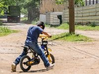 Five-year-old David Rojas rides his bike in front of his family's home on Bird Lane in the Floral Farms neighborhood of southeast Dallas. Eighteen-wheelers and other commercial trucks use the narrow street many times daily to get to an industrial recycling and waste disposal site on Bird Lane.