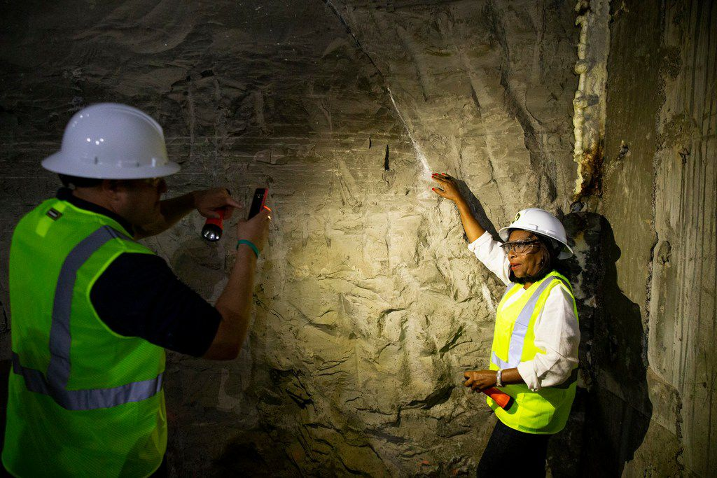 Dallas City Council member Adam Medrano takes a picture of Carolyn King Arnold as she touches the fault line  during a visit into the Mill Creek Drainage Relief Tunnel.