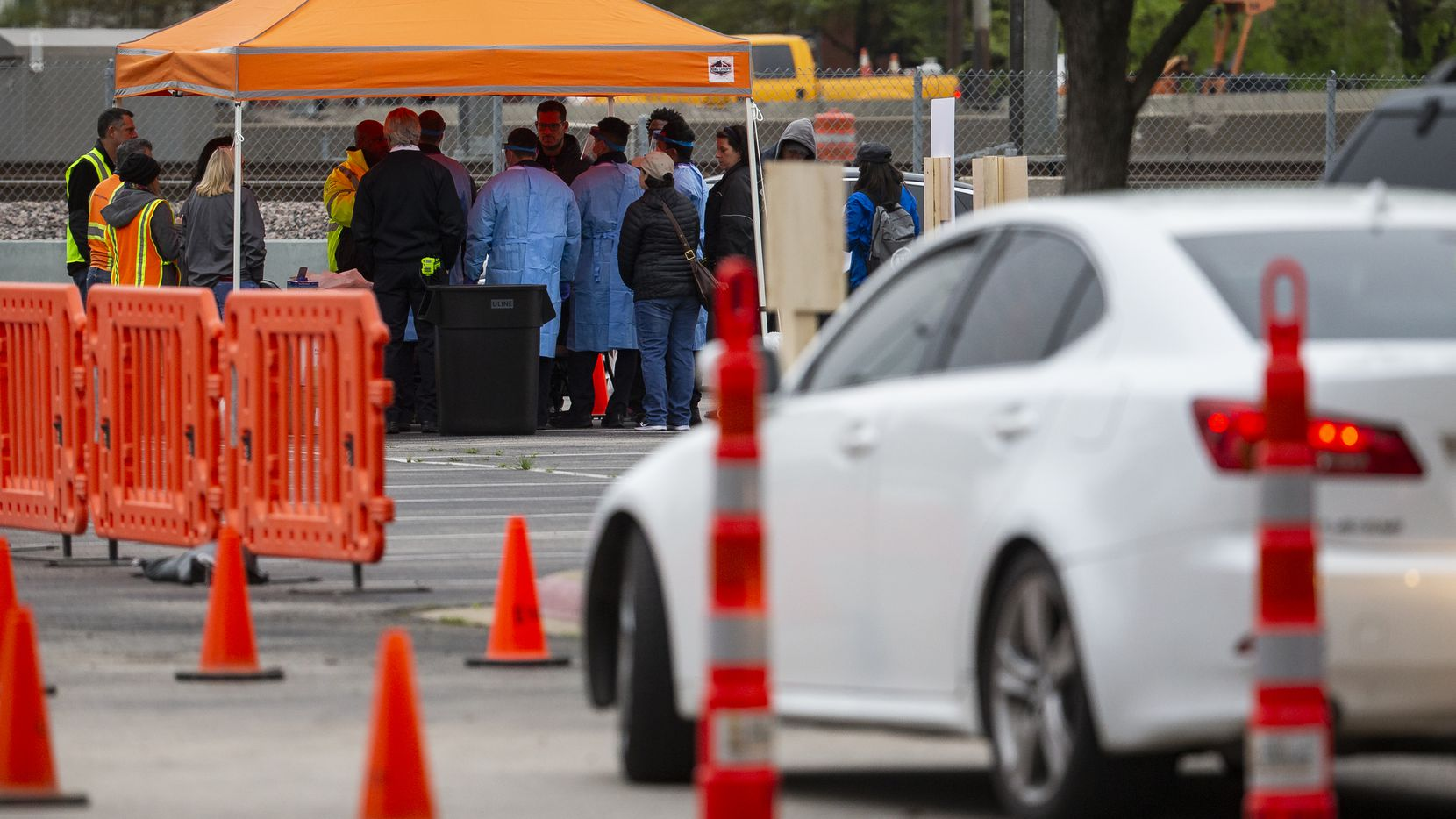 People wait in their cars for screening at the COVID-19 testing site. Strict criteria were in place for who would be cleared for a test.