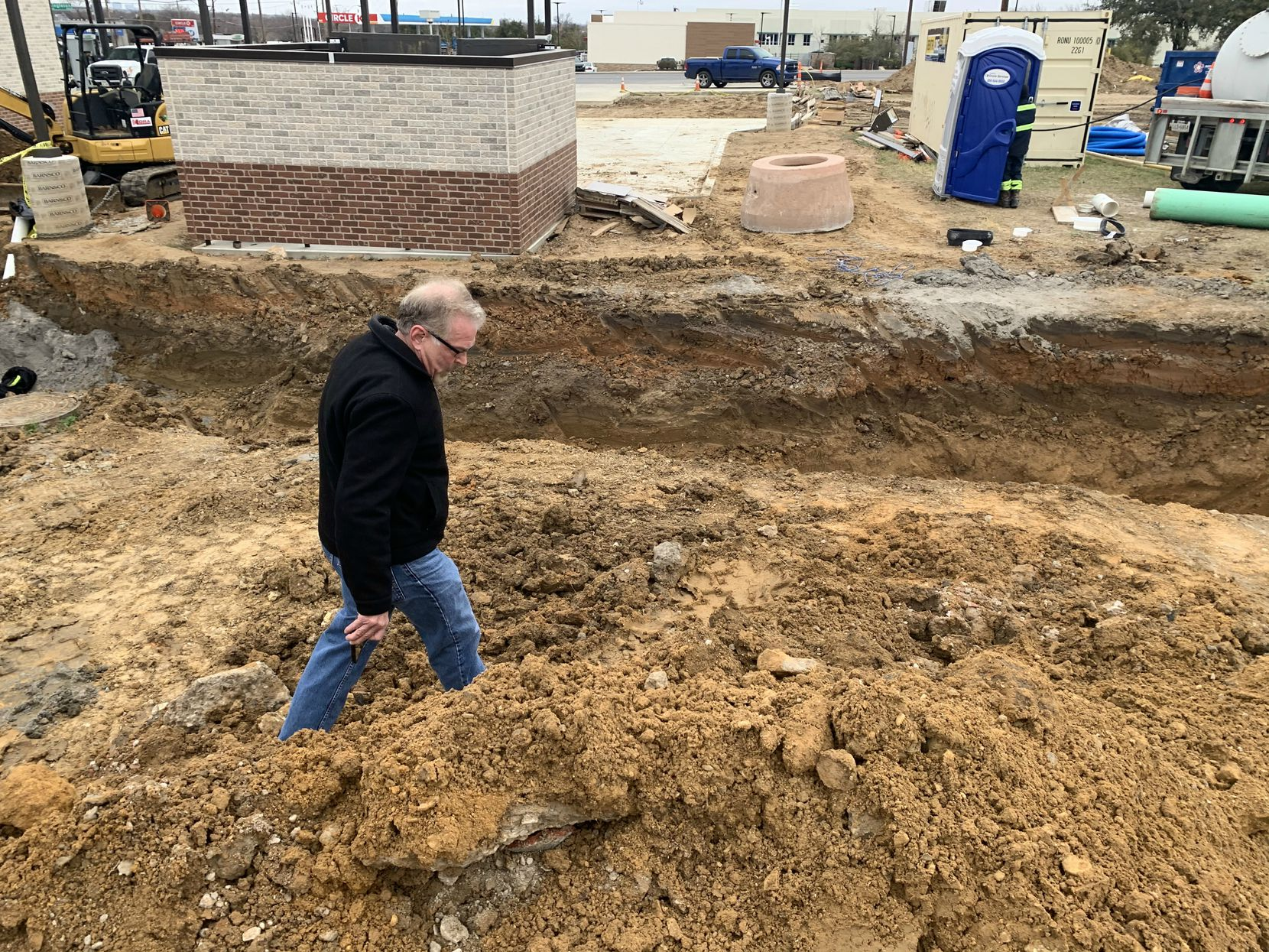 Downwinders at Risk founder Jim Schermbeck inspects mounds of dirt along an open trench on the former RSR Corp. lead smelter site in West Dallas.