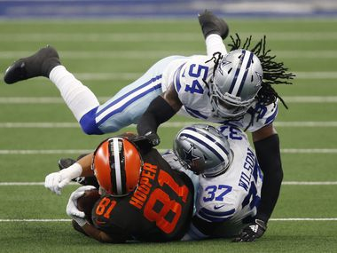 Dallas Cowboys middle linebacker Jaylon Smith (54) grabs the face mask of Cleveland Browns tight end Austin Hooper (81) as Dallas Cowboys safety Donovan Wilson (37) tackles him during the first quarter of play at AT&T Stadium in Arlington, Texas on Saturday, October 4, 2020. Face mask penalty was called on the play.