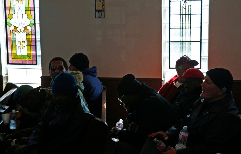 People pray during worship service at SoupMobile Church for the homeless in Dallas on Feb. 4, 2018.