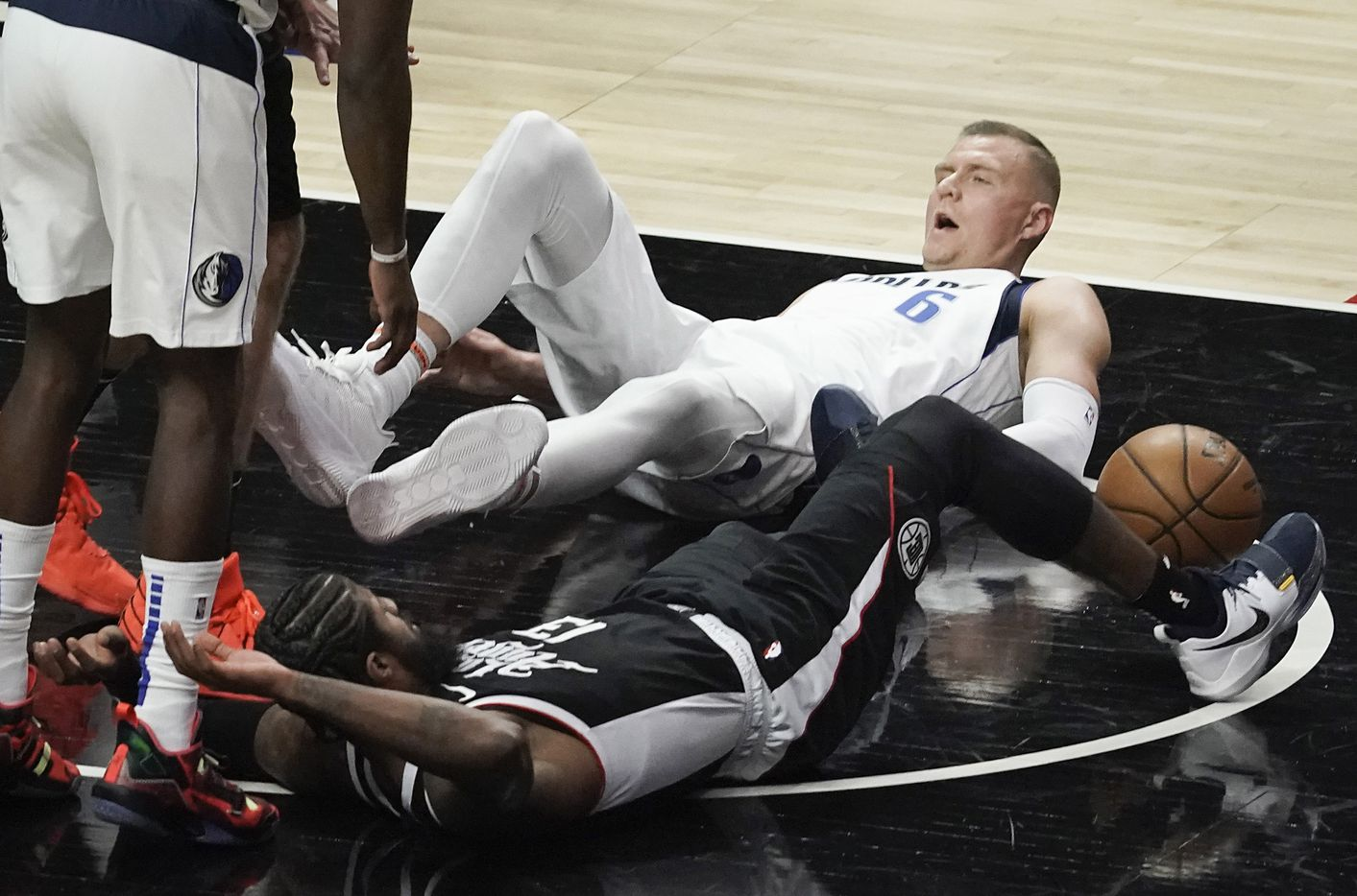 Dallas Mavericks center Kristaps Porzingis (6) tumbles to the court with LA Clippers guard Paul George (13) during the first half of an NBA playoff basketball game at Staples Center on Saturday, May 22, 2021, in Los Angeles.