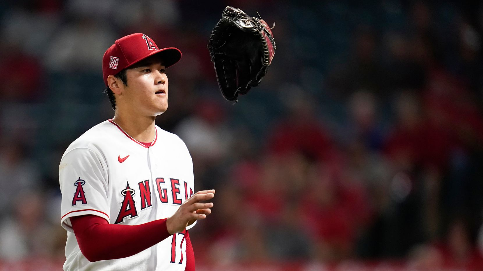 Los Angeles Angels starting pitcher Shohei Ohtani (17) tosses his glove as he returns to the dugout in the middle of the fourth inning of a baseball game against the Texas Rangers Friday, Sep. 3, 2021, in Anaheim, Calif. (AP Photo/Ashley Landis)