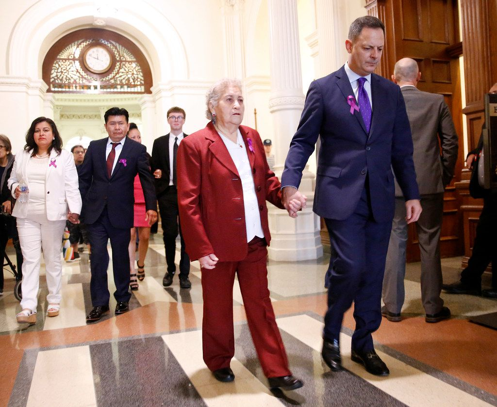 """Representative Rafael Anchia, D-Dallas (right) escorts Amparo Camacho, grandmother of 12 yr-old Linda """"Michellita"""" Rogers, and the rest of the family in attendance (background) to his House of Representatives office at the Texas State Capitol in Austin, Wednesday, February 27, 2019.  """"Michellita""""'s mother Linda Rogers (left) and father Jose Fiscal joined them.  """"Michellita"""" died when their home exploded following a natural gas leak a year ago. (Tom Fox/The Dallas Morning News)"""